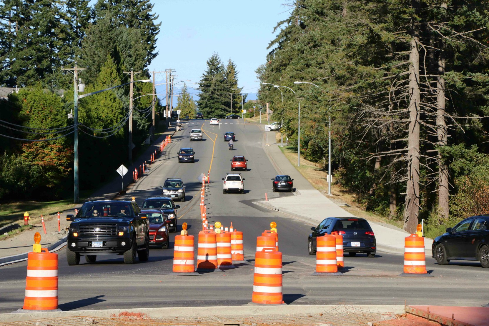 A typical roadway construction zone in British Columbia marked with Orange and Black signs, pylons and markers (photo by WestCoastDriverTraining.com)