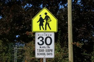 School Zone sign (Advisory) with regulatory sign attached for posted 30 km/h speed limit. Note that this sign contains hours the School Zones is in effect, in this case 7:30 a.m. to 5 p.m. on School Days (photo by WestCoastDriverTraining.com)