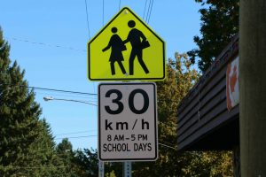 School Zone sign (Advisory) with regulatory sign attached for posted 30 km/h speed limit. Note that this sign contains hours the School Zones is in effect, in this case 8:00 a.m. to 5 p.m. on School Days (photo by WestCoastDriverTraining.com)